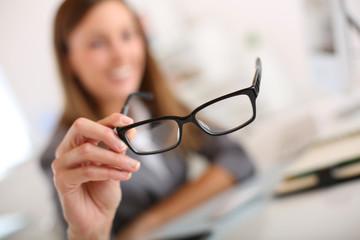 Closeup of eyeglasses held by businesswoman