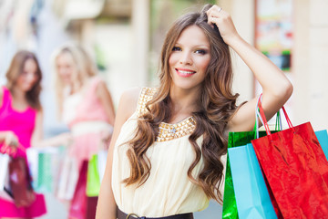 Shopping woman holding bags with friends at the background