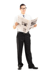 Businessman standing and reading a newspaper