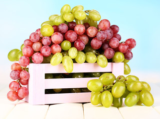 Ripe green and purple grapes in wooden box