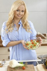 Attractive woman making salad