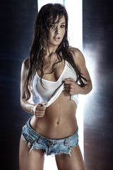Wall Mural - Beautiful young lady posing in wet clothes.