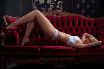 Sensual hot girl on red sofa