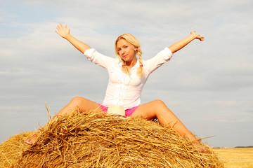 Beautiful woman near haystack
