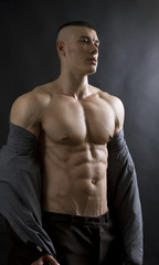 Young sexy man with athletic body on black background.