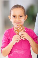 little girl eating fresh baked gingerbread cookie
