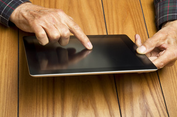 The grandfather use the tablet in relax
