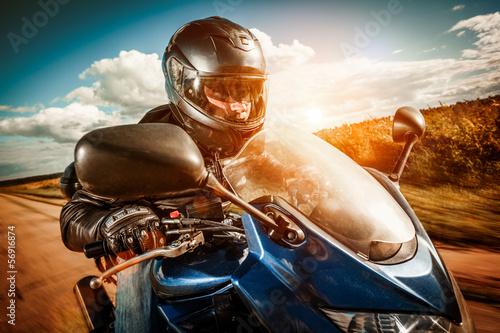 Fototapete Biker racing on the road