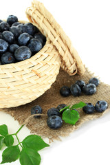 Blueberries in wooden basket on sackcloth isolated on white