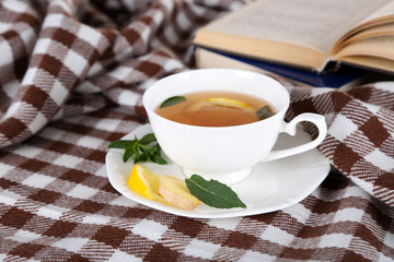Cup of tea with ginger on plaid with a book