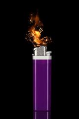Cigarette lighter with sparks/flame on black.