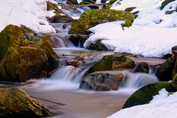 small stream with snow and ice in winyter