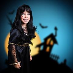 kleines Mädchen im Hexenkostüm vor Halloweenhaus