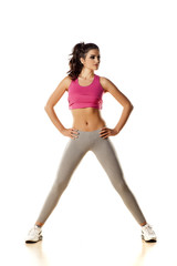 pretty young woman posing during exercise on white background