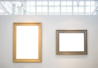 Two empty picture frames on white wall