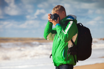 Young man with camera makes sea snapshot