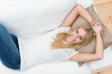 blonde junge frau entspannt zu hause auf dem sofa