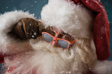 Santa Claus wearing sunglasses dancing outdoors at North Pole