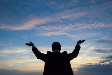 männliche Silhouette hebt die Hände zum Himmel