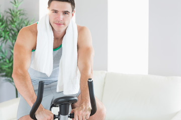 Content handsome man training on exercise bike