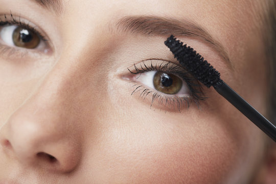 Portrait of young woman applying mascara, close up