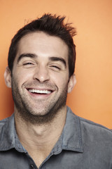 Portrait of mid adult man laughing against orange background