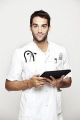 Portrait of mid adult doctor holding tablet