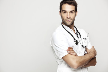 Portrait of mid adult doctor against grey background