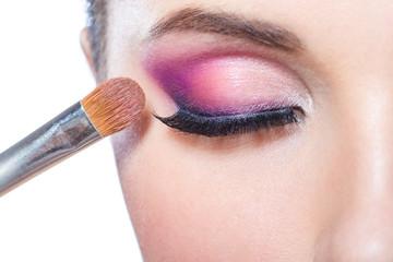 Close up of brush applying bright pink makeup