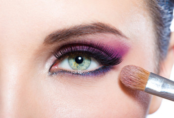 Close up of girl applying bright pink makeup on eye with brush