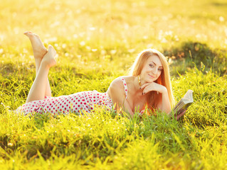 Pretty young woman reading book.