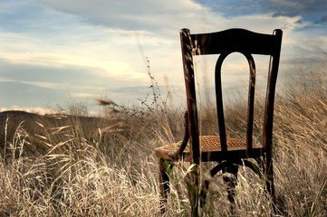 Abandoned chair out in a field