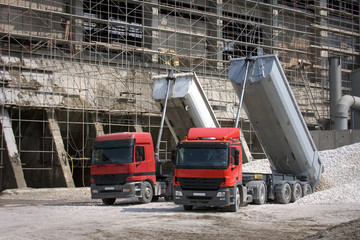 Two big red trucks delivering gravel on construction site