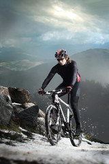 Wall Mural - Cyclist climbing on a rock