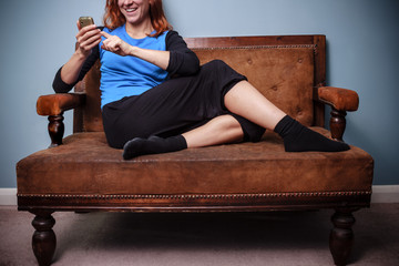 Happy young woman sitting on old sofa using her phone