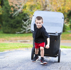 Young boy bringing trash can up the driveway