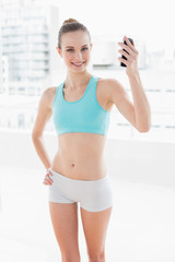 Sporty smiling woman holding up smartphone