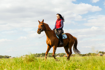 Photo sur Toile Equitation Young woman riding a horse