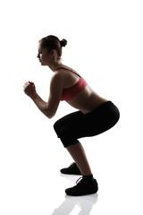sport girl doing squatting exercise, silhouette studio shot over