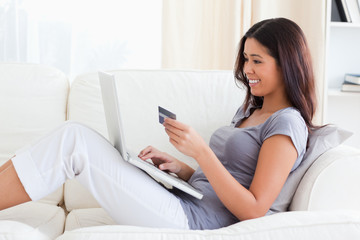 smiling woman sitting on sofa holding creditcard