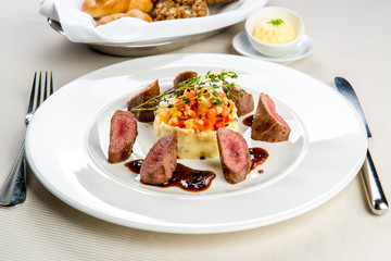 Beef and mashed potatoes decorated with vegetables