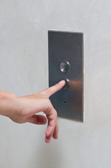 Woman's hand pushing elevator button to go down