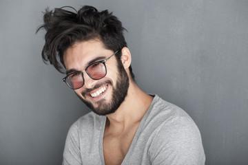 Obraz sexy man with beard smiling big against wall - fototapety do salonu