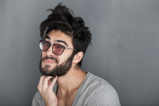 sexy man rubbing his beard against wall