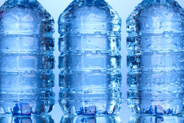 plastic bottles of water close-up on blue background