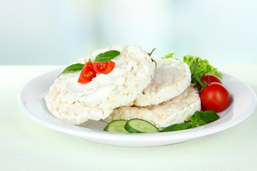 Tasty crispbreads with vegetables on white table