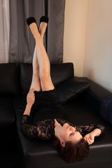 Frau auf Sofa streckt Beine hoch