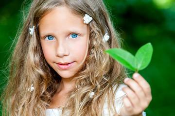 Blue eyed girl holding green leaf.