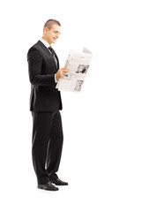 Full length portrait of a young businessman reading a newspaper