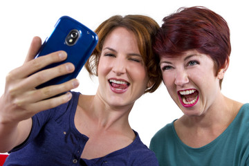two women taking self portraits with a cell phone